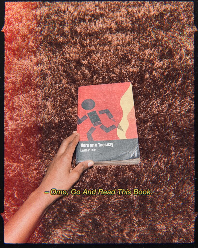 Handheld copy of Born On A Tuesday by Elnathan John on a